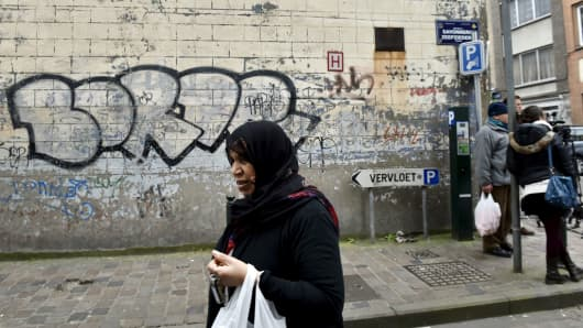 A woman walks by in the Brussels district of Molenbeek, March 19, 2016.
