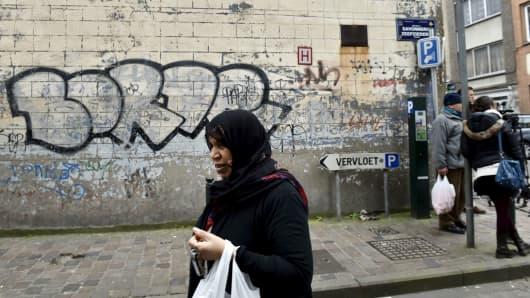 A woman walks by in the Brussels district of Molenbeek, March 19, 2016.