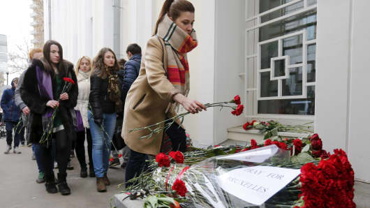 People place flowers for the victims of the Brussels attacks, in front of the Belgian embassy in Moscow, Russia, March 22, 2016.