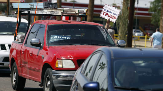 A Donald Trump supporter holds a sign out his window as he drives past a campaign rally for Democratic presidential candidate Hillary Clinton at Carl Hayden High School