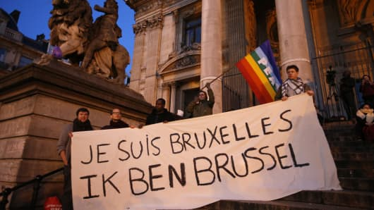 "People display a solidarity banner on the steps of the old stock exchange building in Brussels following bomb attacks in Brussels, Belgium, March 22, 2016. Banner reads ""I am Brussels"" in French and in Flemish languages."