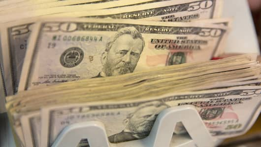 U.S. fifty dollar bills are run through a counting machine inside a currency exchange store in Mexico City, Mexico.