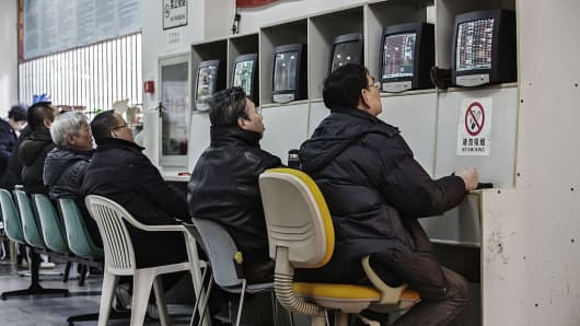 Men sit at trading terminals displaying share prices at a securities exchange house in Shanghai, China.