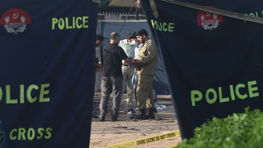 Pakistani security officials collect evidence at the cordoned-off site of the March 27 suicide bombing, in Lahore on March 28, 2016.