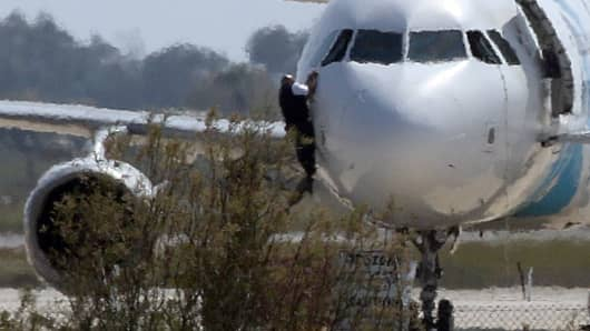 A man climbs out of the cockpit window of the hijacked Egyptair Airbus A320 at Larnaca Airport in Larnaca, Cyprus, March 29, 2016.