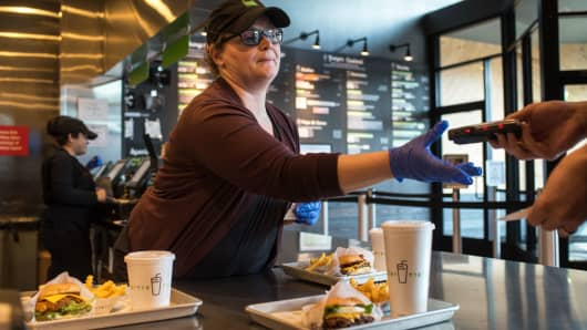 A worker takes a pager from a customer at a Shake Shack restaurant in Bridgewater, New Jersey.