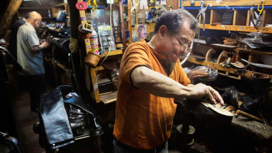Employee Luis Reyes repairs shoes at the workshop of Jim's Shoe Repair in New York, March 11, 2015.