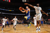 Stephen Curry #30 of the Golden State Warriors lays up a shot against Will Barton #5 of the Denver Nuggets at Pepsi Center on January 13, 2016 in Denver, Colorado. The Nuggets defeated the Warriors 112-110.