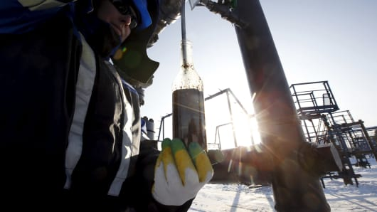 A worker takes oil samples from a well at the Gazpromneft-owned Yuzhno-Priobskoye oil field outside the West Siberian city of Khanty-Mansiysk, Russia.