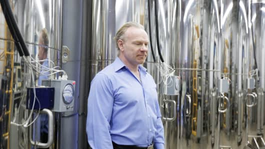 Alcor CEO Max More poses in front of the dewars that house his 147 cryopreserved patients.
