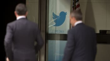 Men walk past the Twitter Inc. logo