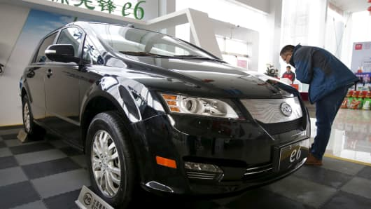 A customer checks a BYD e6 electric car at a dealership in Beijing, China.