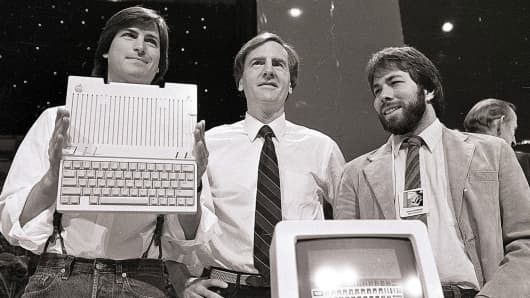 Steve Jobs, as Apple Computers chairman, John Sculley, as president and CEO, and Steve Wozniak, co-founder (l-r) unveiling the Apple IIc computer in San Francisco on April 24, 1984.