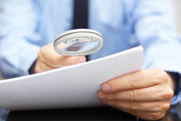 Businessman looking at documents with magnify glass