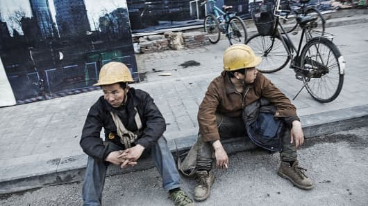 Workers sit on the pavement near a construction site in Beijing, China, on Wednesday, March 2, 2016.