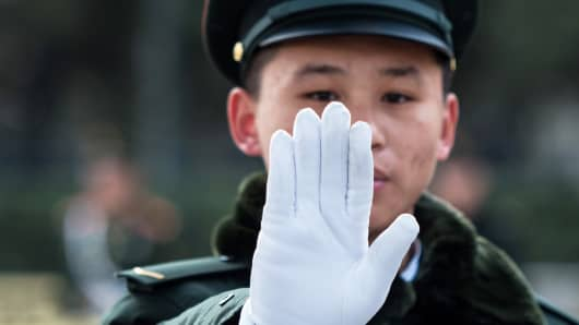 A security guard gestures outside the Great Hall of the People in Beijing, China.