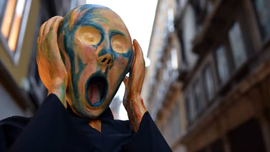 A costumed reveller wearing a mask depicting Munch's famous painting 'The Scream' poses near St Mark's square during the carnival on February 21, 2014 in Venice.