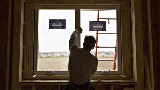 A contractor supports a window as it is installed inside a new home under construction in Dunlap, Illinois.
