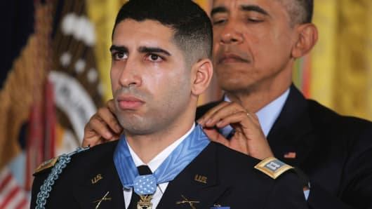 President Barack Obama (R) presents the Medal of Honor to retired Army Captain Florent Groberg during an East Room ceremony at the White House on November 12, 2015, in Washington, D.C.