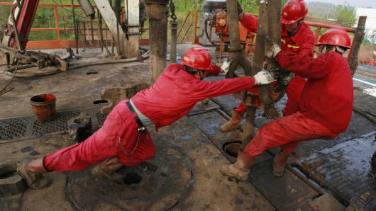 Labourers work at a well head in a PetroChina oil field in Tongnan, southwest China's Sichuan province