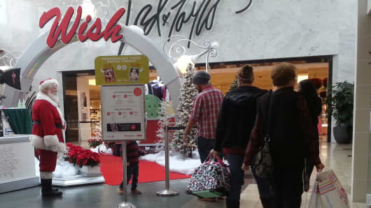 Shoppers walk past the Santa Claus photo booth in at the Westfield Mall in Annapolis, Maryland.