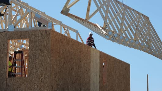 Workers install roof trusses on a home under construction in the Copperleaf development in Centennial, CO.