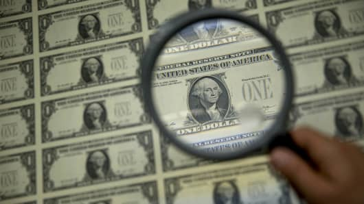A magnifying glass is held over a 50 subject one dollar note sheet after being printed by an intaglio printing press