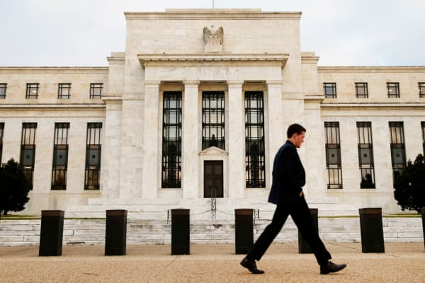 A pedestrian walks outside the Federal Reserve Bank building in Washington.