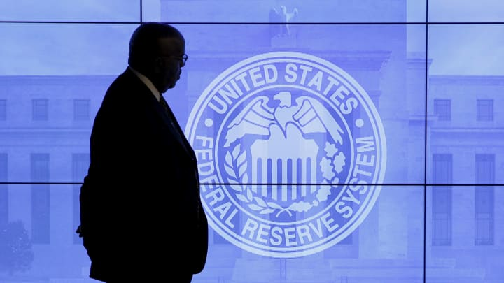 A security guard walks in front of an image of the Federal Reserve in Washington.