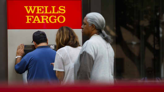 Customers wait in line for an ATM outside of a Wells Fargo & Co. bank branch in Los Angeles, California.