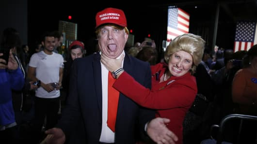 Supporters of Democratic U.S. presidential candidate Hillary Clinton, who came to her rally in costume as Republican presidential candidate Donald Trump (L) and as Mrs. Clinton (R), clown around as they attend her Super Tuesday night party in Miami, Florida, March 1, 2016.