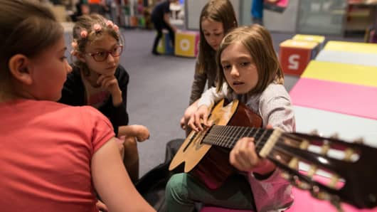 Girls playing guitar at a summer camp