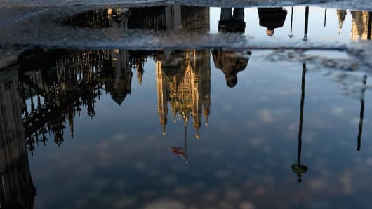 Londoners walk past the Houses of Parliament, reflected in a puddle of rain in Westminster, following the EU referendum on June 24, 2016, in London, England.