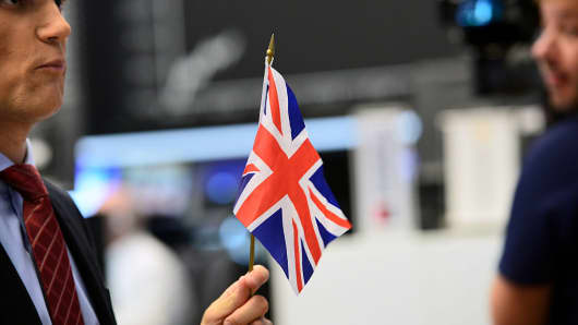 A TV reporter stands with a Great Britain flag at the Frankfurt Stock exchange the day after a majority of the British population voted for leaving the European Union on June 24, 2016.