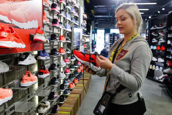 An employee laces a trainer, manufactured by Nike Inc., at a JD Sports Fashion Plc sportswear retail store on Oxford Street in London, U.K