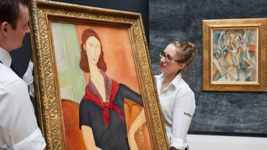 Masterpieces by Modigliani and Picasso unveiled at Sotheby's on June 16, 2016 in London. (L-R) Modigliani's Jeanne Hebuterne (au foulard), 1919 and Picasso's Femme assise, 1909 were auctioned as part of the Impressionist & Modern Art Evening sale.