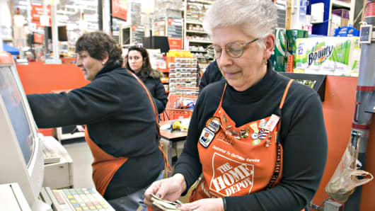 A cashier counts a customers money as she works the register inside a Home Depot in Somerville, Massachusetts.