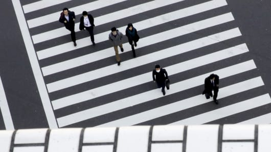 People cross a street in a business district in Tokyo, Japan.