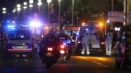 Police officers and rescue workers arrive to assist the crowd that a truck drove through during Bastille Day celebrations in Nice, France.