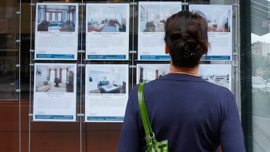 A customer looks at listings on display outside a Brown Harris Stevens offices in New York.