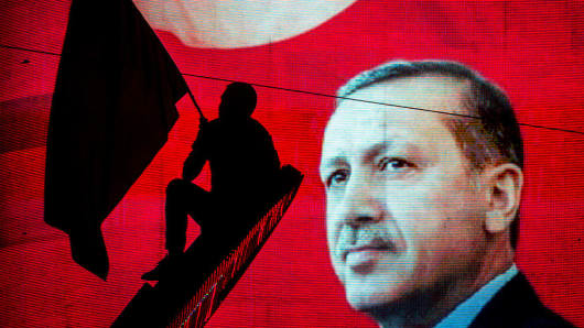 A supporter of Turkish President Recep Tayyip Erdogan waves a flag against an electronic billboard during a rally in Kizilay Square on July 18, 2016, in Ankara, Turkey.