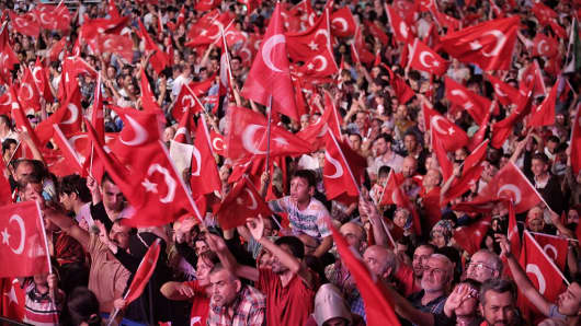 Supporters of Turkish President Recep Tayyip Erdogan wave Turkish flags as they gather in Istanbul's central Taksim Square on July 19, 2016, in Istanbul, Turkey.