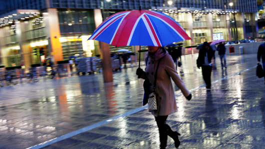 Pedestrians walk in the rain at the Canary Wharf business district in London.