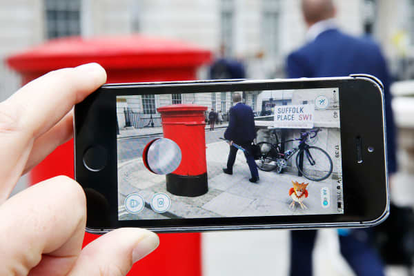 "A user playing ""Pokemon GO"" on a London street."