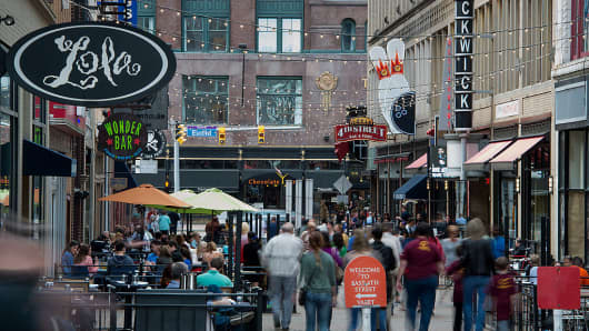 Pedestrians walk past restaurants and shops on East 4th Street in downtown Cleveland.