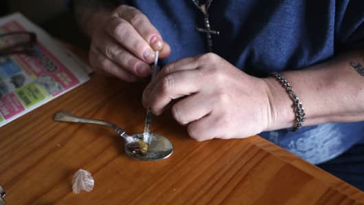 A heroin user prepares to inject himself in New London, Conn.