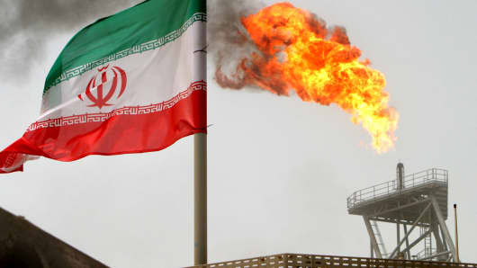 A gas flare on an oil production platform is seen alongside an Iranian flag in the Gulf.