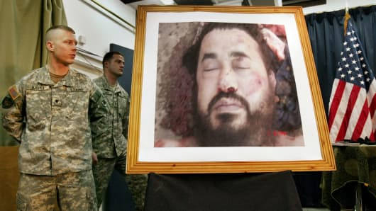 A U.S. soldier at a press conference in Baghdad, Iraq looks across at a photo purporting to show the body of Abu Musab al-Zarqawi, June 8, 2006.