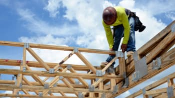 A construction worker sets a floor truss in place that will support the second story of a home at a Lennar development in Doral, Florida.