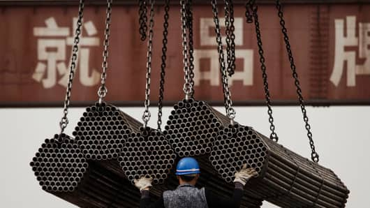 A Chinese steel worker helps load steel rods onto a large truck for transport at a plant